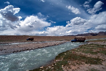 Trucks crossing a gushing river
